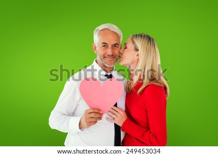 Handsome man holding paper heart getting a kiss from wife against green vignette - stock photo
