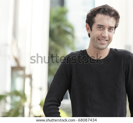 Handsome man in a black shirt smiling - stock photo