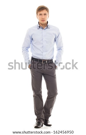 Handsome man in a blue shirt holds his hands in pockets over a white background - stock photo