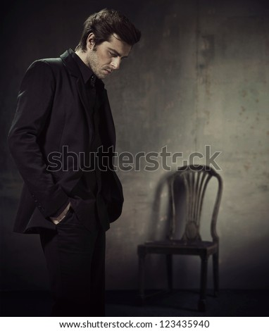 handsome man in a business suit on a dark background - stock photo