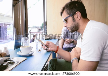 Handsome man in a coffee shop, relaxing, vintage retro look - stock photo