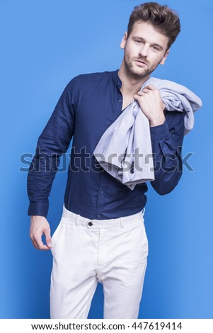 Handsome man in a dark blue shirt on a blue background - stock photo