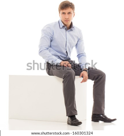 Handsome man in a shirt and trousers is sitting on a cube - stock photo