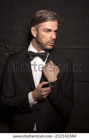 handsome man in a suit and bow tie on a black wall  - stock photo