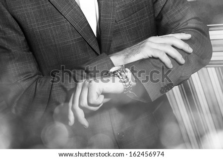 Handsome man in a suit is looking at his watch. The photo is black and white - stock photo