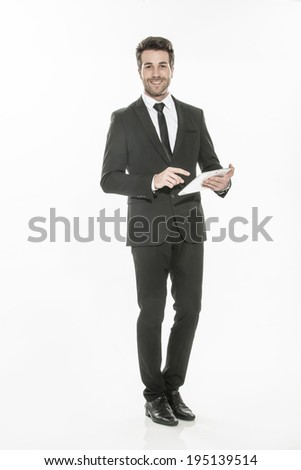 handsome man in a suit using a digital tablet on isolated background - stock photo