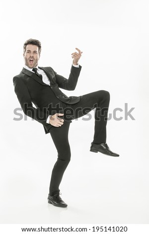 handsome man in a suit who pretends to play the guitar - stock photo