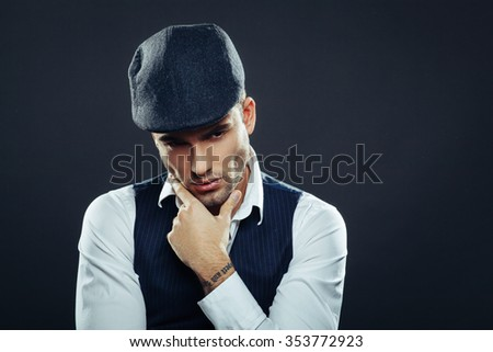 Handsome man in a vest and cap in studio on dark background
