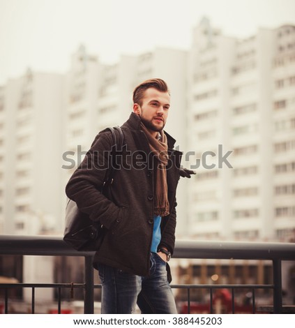 handsome man in an autumn coat posing on the background of buildings