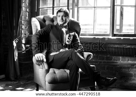 Handsome man in black formal suit with bow-tie sitting in armchair. Black and white fashion style portrait