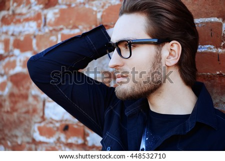 Handsome man in black jacket and spectacles posing outdoor by a brick wall. Men's beauty, fashion. Business style.  - stock photo
