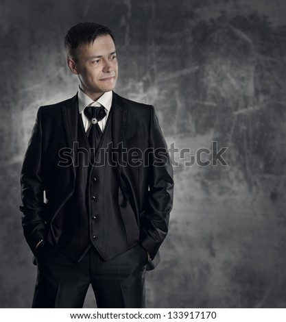 Handsome man in black suit. Wedding groom fashion. Gray background.