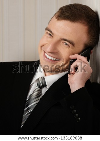 Handsome man in black suit with cell phone talking