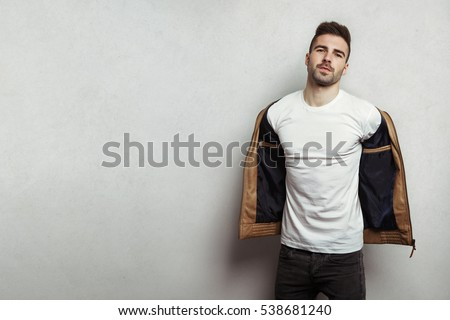 Handsome man in blank t-shirt taking off his leather jacket, grey concrete wall background