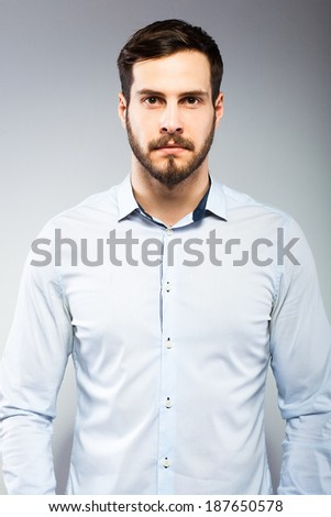 handsome man in blue shirt on grey background - stock photo
