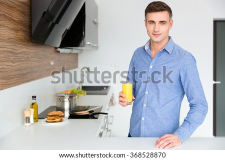 Handsome man in blue shirt standing on the kitchen and drinking orange juice - stock photo