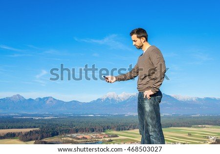 Handsome man in casual clothes, standing on the top of the mountain, using the cell phone on a beautiful panorama of the European alps background