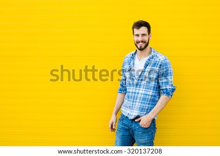 handsome man in checkered shirt smiling on yellow background - stock photo
