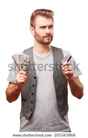 Handsome man in doubt with banking card and cash in his hands isolated on white background. - stock photo