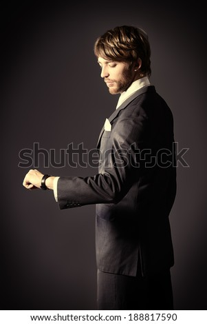 Handsome man in elegant black suit watching at his wristwatch. Over dark background. - stock photo