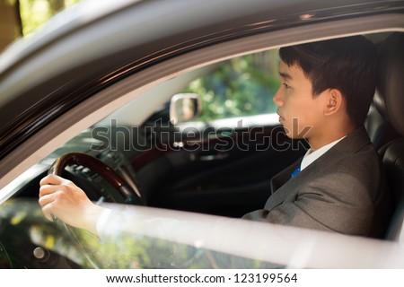Handsome man in elegant formalwear driving a car - stock photo