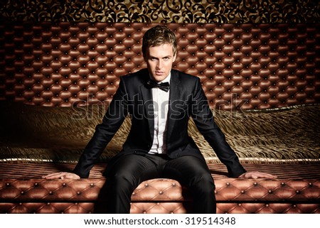 Handsome man in elegant suit sitting on a bed. Luxury. Vintage interior. - stock photo