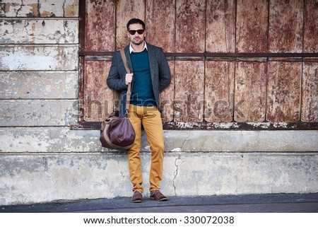 Handsome man in fashionable clothes carrying a travel bag and standing on an urban street in front of a background of rough textures - stock photo