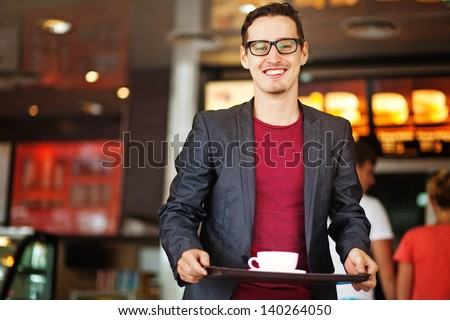 handsome man in fastfood restaurant - stock photo