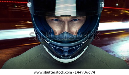 Handsome man in helmet at night in the city - stock photo