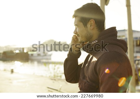 Handsome Man In Hoodie Talking On Mobile Smart Phone Outdoor At River Bank - stock photo
