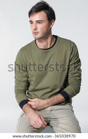Handsome man in jeans and sitting on a cube over a grey background - stock photo
