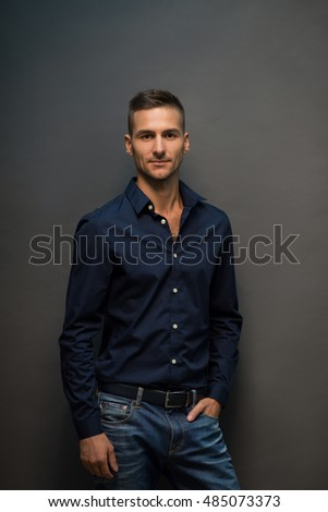 Handsome man in jeans looking at camera and smiling. Fashion or vogue concept. Portrait of model young man in black shirt posing over grey background in studio.