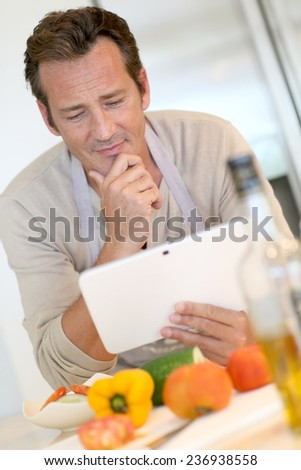 Handsome man in kitchen looking at digital tablet for recipe - stock photo