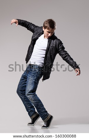 Handsome man in leather jacket, jeans and white t-shirt is dancing over a grey background - stock photo