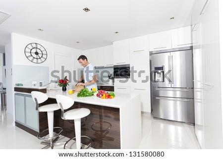 Handsome man in modern kitchen - stock photo