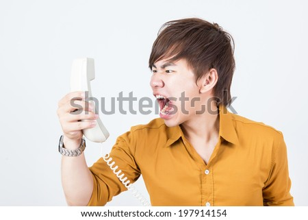 Handsome man in orange shirt shouting to telephone
