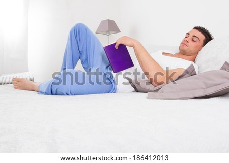 handsome man in pajamas reading book relaxing in his bed