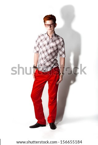 Handsome man in red trousers posing against white background - stock photo