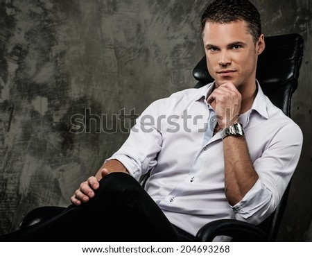 Handsome man in shirt against grunge wall sitting in office chair - stock photo