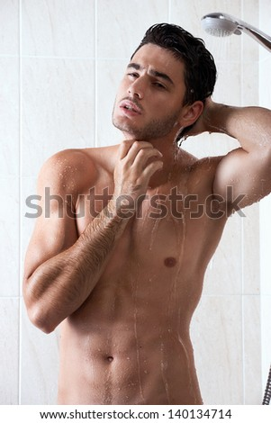 Handsome man in shower - stock photo