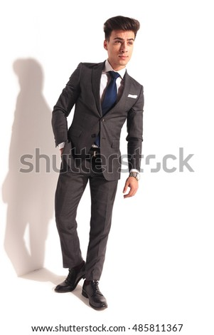 handsome man in suit and tie posing with hand in pocket near studio wall