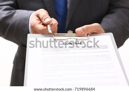 Handsome man in suit offer contract form on clipboard pad and silver pen portrait. Strike a bargain for profit, white collar motivation, union decision, corporate sale, insurance agent concept