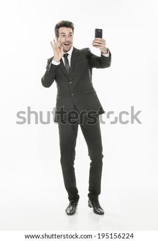handsome man in suit taking a selfie on isolated background - stock photo
