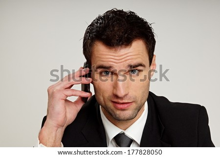 Handsome man in suit talks at mobile phone.