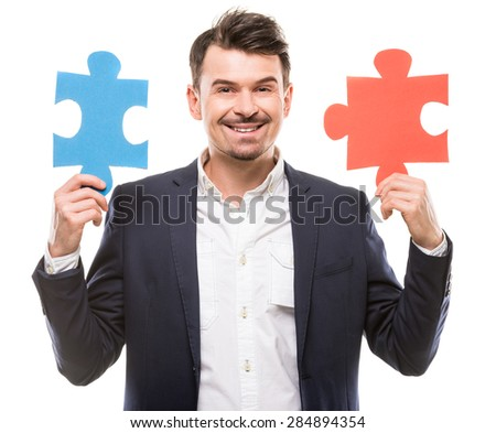 Handsome man in suit trying to connect puzzle pieces.