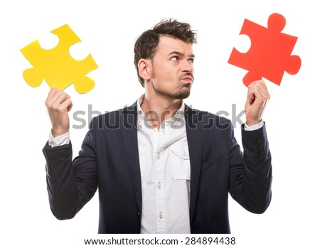 Handsome man in suit trying to connect puzzle pieces. - stock photo
