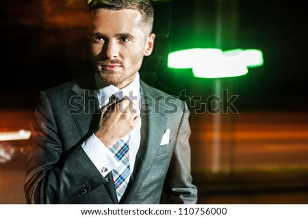 handsome man in suit walks on  night city - stock photo