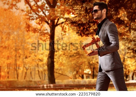 Handsome man in suit with a girt. Autumn. - stock photo