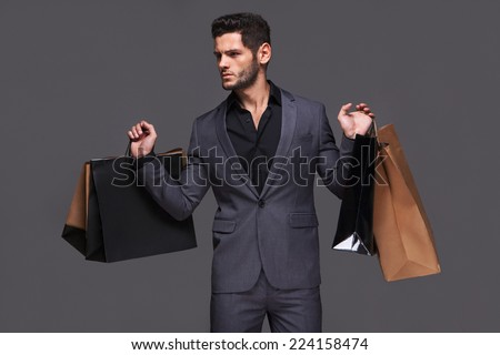 Handsome man in suit with shopping bags - stock photo