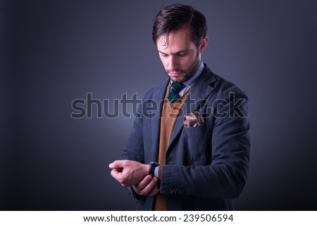 Handsome man in suit with tie and pocket square, looking at his watch, on dark gray background - stock photo